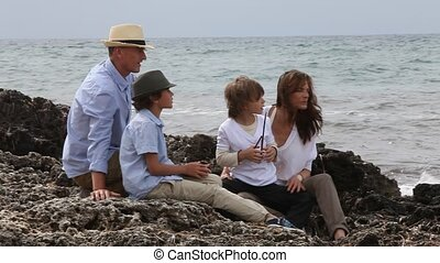 Happy family sitting on a beach