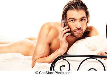 cellphone - Handsome nude man lying in a bed and talking on...