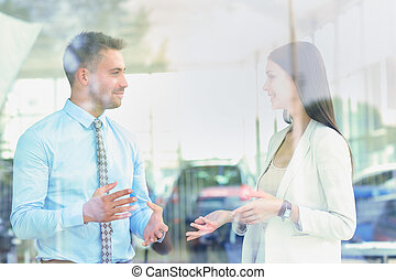 Two cheerful smiling young businesspeople talking at the...