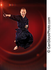 martial arts - Handsome young man practicing kendo Over dark...