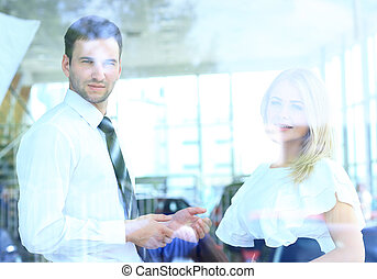 Two cheerful smiling young businesspeople talking at the office. View through window