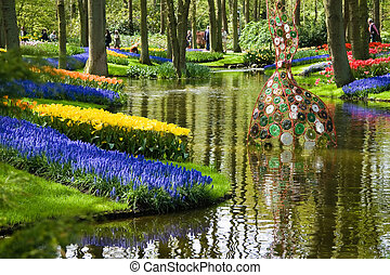 Pond in park in spring with colorful flowers