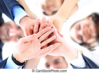 Small group of business people joining hands, low angle view...