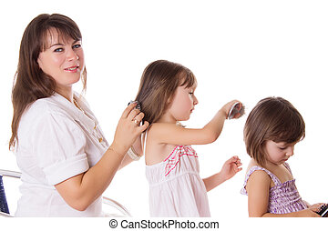 Mother and two daughters combing hair to each othre isolated...