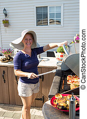 Lady by Outside Kitchen BBQ - Young lady cooking salmon...