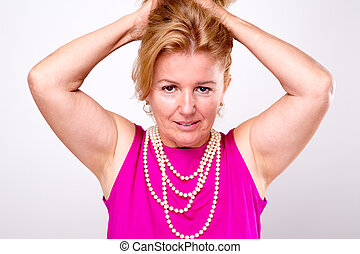Mature Blonde Lady with Both Arms up holding her hair, she...