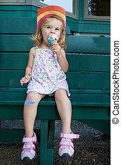Cute little girl eating an ice cream - Cute little blond...