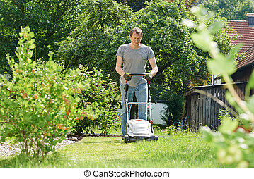 man mowing lawn in backyard - man cutting grass in his...