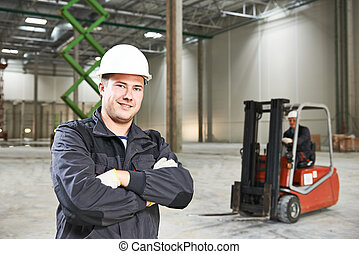 warehouse worker in front of forklift - young smiling...