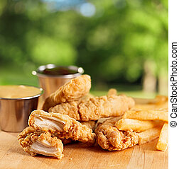 fried chicken strips with french fries and sauce