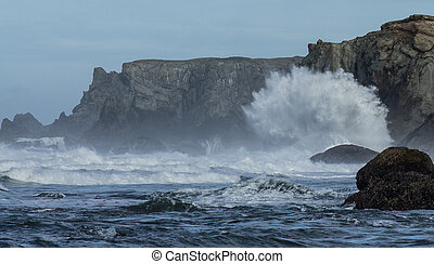 Crashing Wave - A large wave crashes into the cliffed...