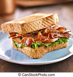 BLT bacon lettuce tomato sandwich with toast off to the...