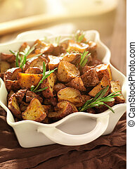 rosemary herb potatoes in white baking dis with sunlight