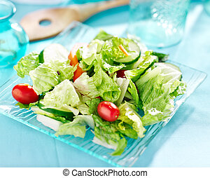 Garden salad with fresh vegetables on glass plate.
