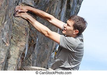 man bouldering - handsome young man bouldering or rock...