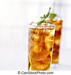 cold iced tea with mint garnish and sliced lemons