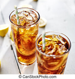 two cold iced tea with straws and lemon slices.