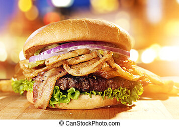 Gourmet hamburger with fried onion straws and cityscape...