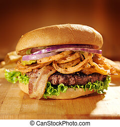 large gourmet hamburger with fried onion straws