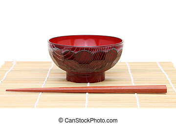 Chopsticks with wooden bowl on bamboo mat