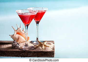 red drink on beach - Tasty red drink on beach with ocean on...