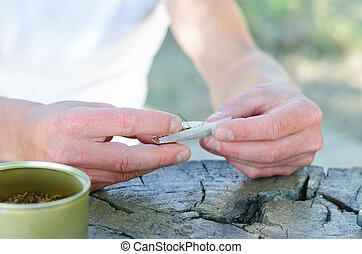 Male hands rolling a cigarette using rollings or a sticky...