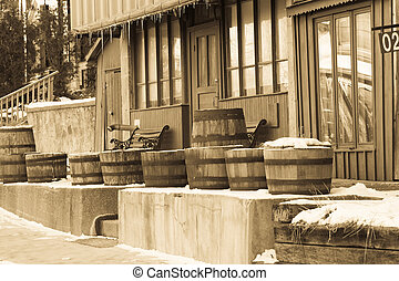 Old West Winter Scene - Wooden barrels outside of an old...