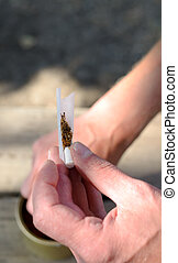 Male hands rolling a cigarette placing the ground tobacco...