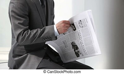 Financial news - Office worker reading financial news in...