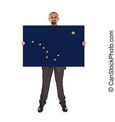 Smiling businessman holding a big card, flag of Alaska,...
