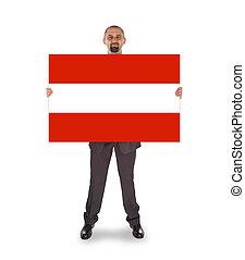 Smiling businessman holding a big card, flag of Austria,...