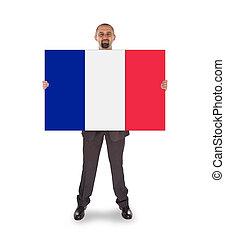 Smiling businessman holding a big card, flag of France,...