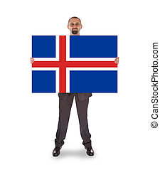 Smiling businessman holding a big card, flag of Iceland,...