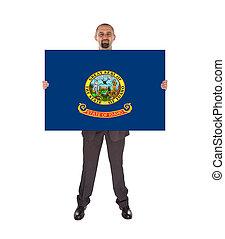 Smiling businessman holding a big card, flag of Idaho,...
