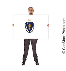 Smiling businessman holding a big card, flag of...