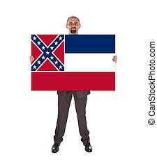 Smiling businessman holding a big card, flag of Mississippi,...