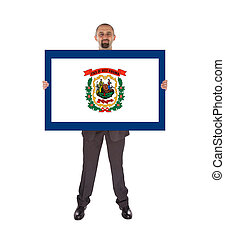 Smiling businessman holding a big card, flag of West...