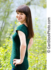 Beautiful young woman in park wearing knitted green blouse