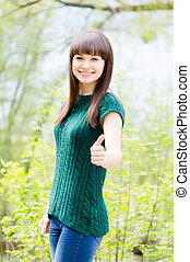 Beautiful young woman in knitted green blouse showing thumbs...