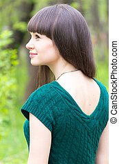 Beautiful young woman in park wearing knitted green blouse...