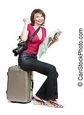 young woman tourist sitiing on the suitcase and holding map