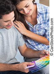 Couple looking at color samples to decorate their house -...