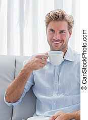 Cheerful man drinking a coffee in the living room
