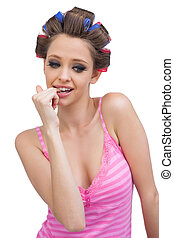 Sexy young model posing wearing hair curlers against white...