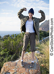 Woman hiking and showing her strength looking at camera in...