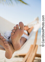 Close up of sandy feet of woman sleeping in a hammock on the...