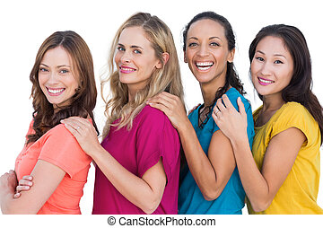 Cheerful models in a line posing with colorful t shirts on...