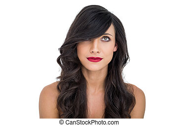 Pretty dark haired woman posing with red lips looking up on...