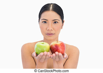 Content natural brunette holding apples in both hands on...