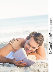 Smiling handsome man on the beach reading - Smiling handsome...
